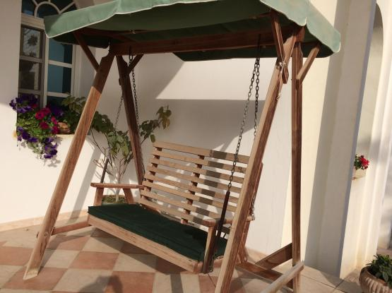 Covered wooden outdoor swing