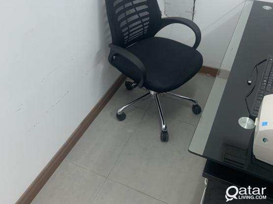 A desk, a swivel chair, and two chairs
